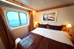 Ship cabin with bed and window with view on sea. Ship cabin with big double bed and window with view on sea summer day Stock Photos