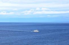Ship in the calm blue sea. Small cruise ship in the calm blue sea Stock Image