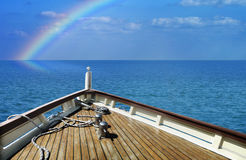 Ship in a calm sea. Rainbow on the horizon. Royalty Free Stock Photography