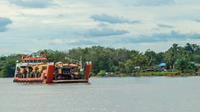 Ship carry heavy machinery for mining purpose cruising Mahakam river. Borneo, Indonesia Stock Photos