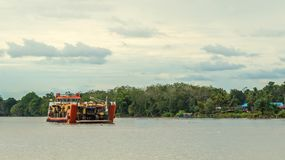 Ship carry heavy machinery for mining purpose cruising Mahakam river. Borneo, Indonesia Royalty Free Stock Photo