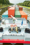 Ship carrying cargo containers on channel Stock Photography