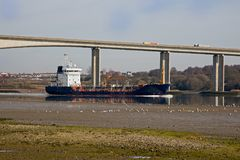 Gas Tanker in the UK. A ship carrying gas passing under a motorway bridge at low tide in the UK Stock Photos
