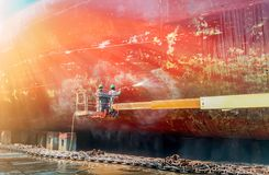 Ship cleaning. Work in floating dry dock with water jet cleans the shipboard and have movement of people of the ship from sea vegetation before sandblast and Royalty Free Stock Photo