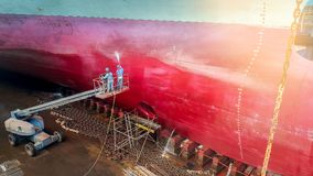 Ship cleaning. Work in floating dry dock with water jet cleans the shipboard and have movement of people of the ship from sea vegetation before sandblast and Royalty Free Stock Images