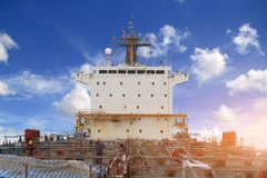 Ship construction. Cargo ship under repair in floating dock with scaffolding and communication radar on acommodation bridge deck,  blue sky background Royalty Free Stock Photography