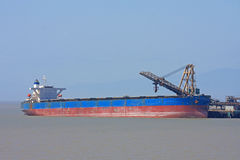 Ship and Crane. Cargo ship and crane in dock Stock Image