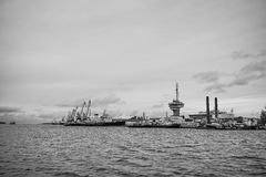 Ship and crane row along the harbor shoreline. View from water Stock Images