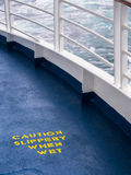 Ship Deck Safety Hazard Warning. Safety warning painted in yellow on the deck of a cruise ship royalty free stock images