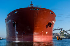 Ship is discharging granite in port. Royalty Free Stock Images