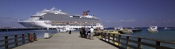 Ship docked in the Caribbean. Cruise ship docked in the Caribbean with passengers walking down the dock to board.  Beautiful view of the ship, framed by the Stock Photos