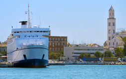 Ship docked in the port of Bari,. In the background the tower of the cathedral royalty free stock photo