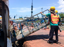 Ship docking. And workers are helping to bridge the boat Stock Image
