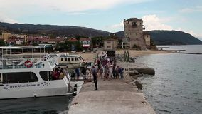 Ship docks to the shore near old tower in Ouranoupoli, Athos peninsula, Greece stock footage