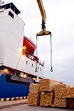 Ship at docks waiting for timber cargo. Crane with slings ready for loading Royalty Free Stock Image