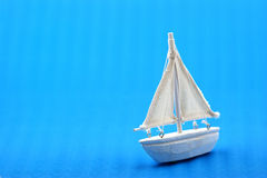 Ship of dreams. Small white boat sailing on blue paper background Stock Images