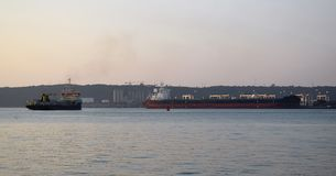 Ship and dredger. A port dredger deepens the channel into the harbor area Durban  SA Royalty Free Stock Image