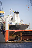 Ship in dry dock. Large container ship rear view with propeller under repair Stock Photos