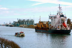 Ship entering a busy industrial harbour. A merchant ship carrying sand entering a busy industrial harbour while three other ships are busy unloading their cargo Royalty Free Stock Image