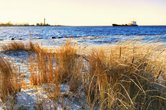 The ship enters the harbor lighthouse in winter Stock Photos