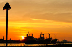 Ship and factory silhouetted at sunset Stock Photography