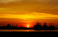 Ship and factory silhouetted at sunset Stock Photo