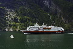 A ship in a fjord. A cruiseboat from the Hurtigruten in the Geiranger fjord at Norway Stock Image