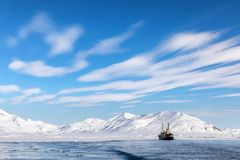 Ship on the fjords of Svalbard. Boat on the fjords of Svalbard, a Norwegian archipelago between mainland Norway and the North Pole, with snowy mountains and blue royalty free stock image