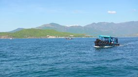 Ship floating in blue sea on green mountain landscape. Boat sailing in turquoise sea water, green mountain and clear sky. On horizon stock video footage