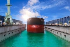 Ship in floating dry dock. Ship in floating dock on blue sky background under ship repair on Monotone Stock Images