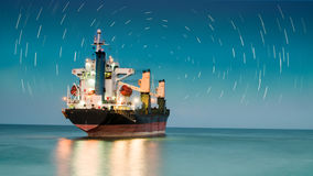 Ship freighter with startail sky. Illuminated cargo boat with startail sky background Stock Photos