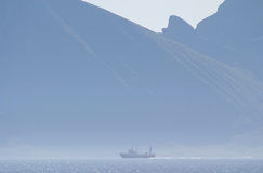 A ship in front of mounts wrapped in mist. A ship in front of the island Austvagøya, one of the islands of the Lofoten in Norway, seen from the ferry boat Stock Photos
