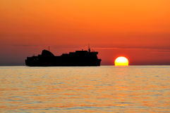 And the ship goes sunset in summertime. A passenger ship in the background of a sunset in summertime,summer stock image