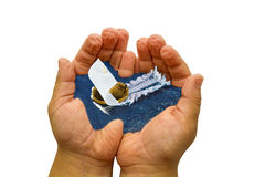 Ship in hands. The ship floats by sea in childrens hands Stock Image