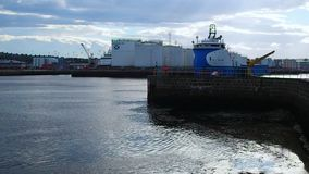 Ship in the harbor. August 2017: Oil support vessel in harbor port operation. You see oil tanks extracted into the sea. August 2017 in Aberdeen stock video