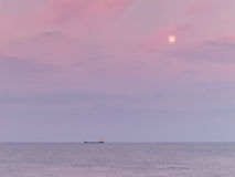 Ship on horizon at dusk Royalty Free Stock Image
