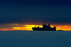 Ship on the icy sea. A container ship is on the way to Helsinki harbor.  There is frozen icy sea in the foreground, and sunrise behind the ship Royalty Free Stock Photos