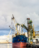 Ship and industrial machines at port. Ship and industrial machines working in the port Stock Image