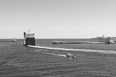 Ship leaves the harbor. Cargo ship leaves the harbor of Valletta. Lighthouses indicate the entrance to the ports of Malta. Black and white picture Stock Photography