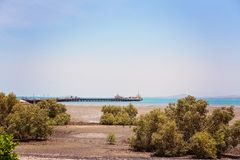 Ship Loading Cargo At A Pier. A ship in the distance loading cargo from a pier at a harbor port royalty free stock photo