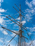Ship mast with housed sails on the blue sky Stock Photo