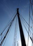 Ship mast. The mast of a traditional sailing ship stands tall into the sky Stock Image