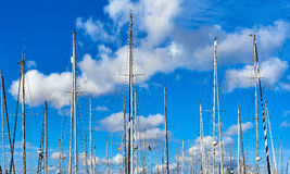 Ship masts against blue cloudy sky. Royalty Free Stock Photos