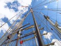 Ship masts beneath blue sky metaphor for smooth sailing Royalty Free Stock Image