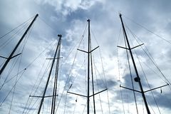 Ship masts. Over blue cloudy sky background stock image