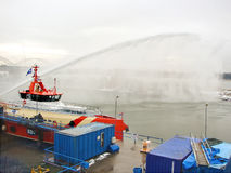 Ship melts the ice by steam gun in the harbor Stock Image