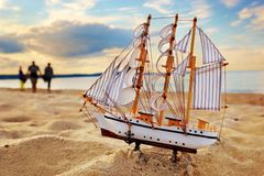 Ship model on summer beach at sunset Stock Photo