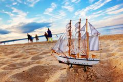 Ship model on summer beach at sunset Stock Photos