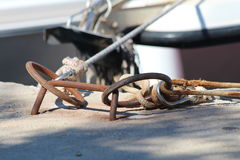 Ship mooring rings. A pair of circular rusting metal boat mooring with ropes tied through securing a boat to the mooring Royalty Free Stock Photos