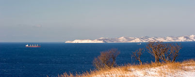 Ship moving by sea along the coast of the mountainous winter. Nakhodka Bay. East (Japan) Sea. 02.01.2013 Stock Images